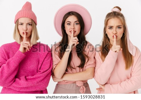 Image of three pretty girls wearing pink clothes keeping fingers Stock photo © deandrobot