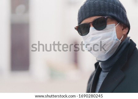 Sideways shot of man in hat, sunglasses and protective mask, reads newspaper outdoor, poses at stree Stock photo © vkstudio