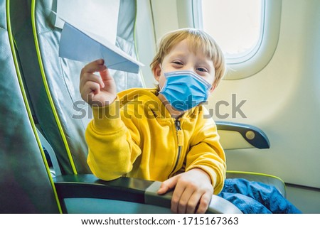 Little boy play with paper plane in the commercial jet airplane flying on vacation Tourists fear the Stock photo © galitskaya