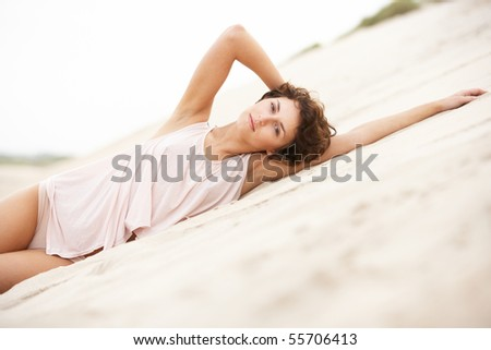 Fashionably Dressed Attractive Young Woman Laying Amongst Sand D Stock photo © monkey_business