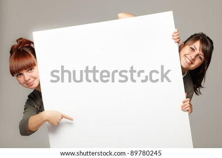 image of two young women smiling and holding empty placard with stock photo © deandrobot