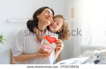 Happy mother with her baby daughter in the living room at home Stock photo © Lopolo