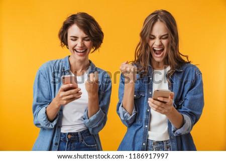 Fiatal nők barátok izolált citromsárga fal beszél Stock fotó © deandrobot