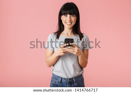 Happy cheerful young woman posing isolated over pink wall background holding feather leaf. Stock photo © deandrobot