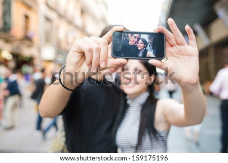 Photo of cute couple man and woman taking selfie on mobile phone Stock photo © deandrobot