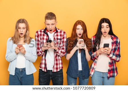 Shocked young group of friends students standing isolated over white wall background. Stock photo © deandrobot