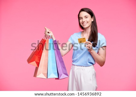 Young cheerful shopper with several paperbags showing plastic card Stock photo © pressmaster