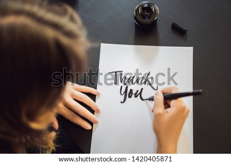 Calligrapher Young Woman writes phrase on white paper. Inscribing ornamental decorated letters. Call Stock photo © galitskaya