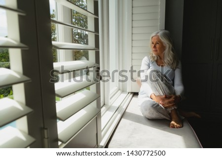 Front view of a thoughtful senior woman looking through window at home Stock photo © wavebreak_media