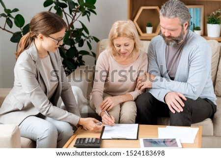 Young agent pointing at place for signature while mature client signing document Stock photo © pressmaster