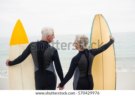 Rear view of senior male surfer standing with surfboard on the beach with mountains in the backgroun Stock photo © wavebreak_media