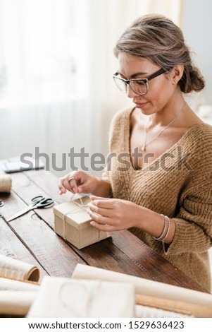 Young female in casualwear and eyeglasses binding wrapped giftbox with threads Stock photo © pressmaster
