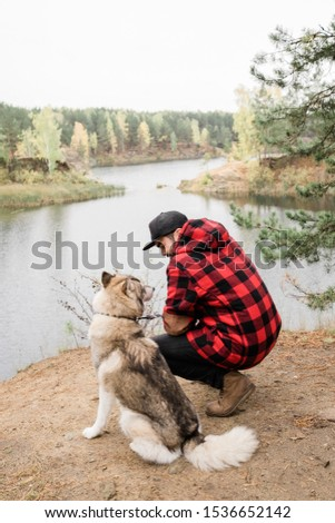 Stock photo: Young man in checkered jacket and black jeans sitting on squats by purebred pet