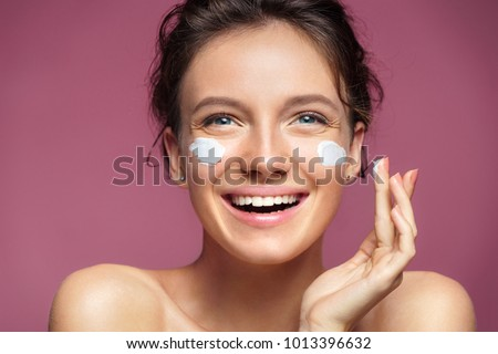 Healthy young woman with toothy smile touching her clean hydrated radiant face Stock photo © pressmaster