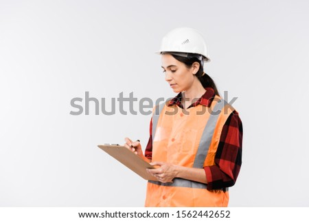 Female builder in hardhat, flannel and working vest making notes in document Stock photo © pressmaster