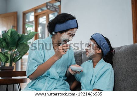 Young mother and her little daughter sitting close to each other by served table Stock photo © pressmaster