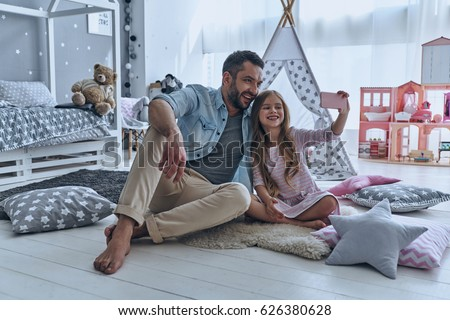 Young man with his little daughter looking at one of decorative toy balls Stock photo © pressmaster