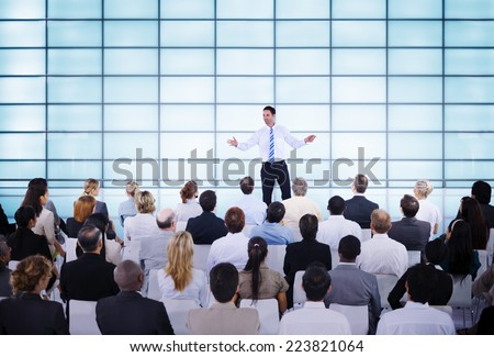 Rear view of Caucasian businessman giving presentation in front of audience in auditorium Stock photo © wavebreak_media