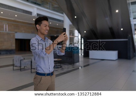 side view of young asian male executive taking selfie with mobile phone standing in the lobby at off stock photo © wavebreak_media