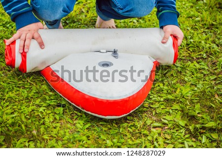 A man blows and collapses SUP A man blows and collapses SUP. Leisure and outdoor sports concept Stock photo © galitskaya
