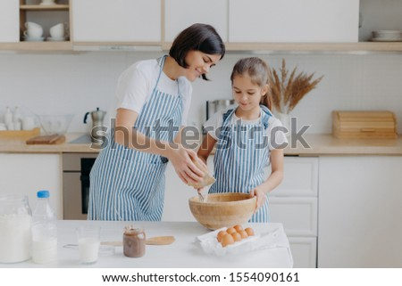 Daughter and mother love cooking, dressed in striped aprons, prepare delicious dinner, use different Stock photo © vkstudio