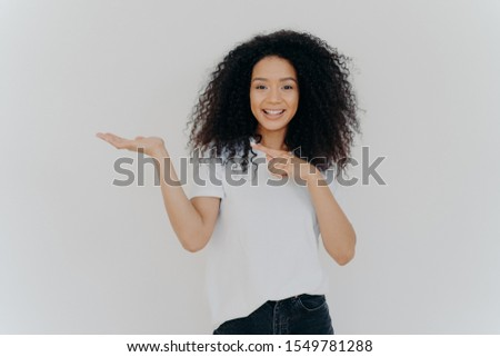 Choice is simple. Attractive feminine girl with Afro hair raises palm and points on blank space, mak Stock photo © vkstudio