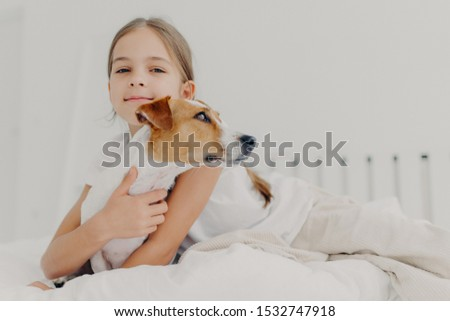 Little girl embraces small pedigree dog, stay in bed, plays with favourite pet before sleep, has app Stock photo © vkstudio