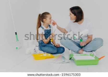 Happy brunette woman plays with daughter, have fun after painting and refurbishment of room, smeark  Stock photo © vkstudio