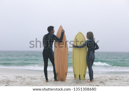 Rear view of young multi-ethnic couple surfer holding surfboards on the beach Stock photo © wavebreak_media