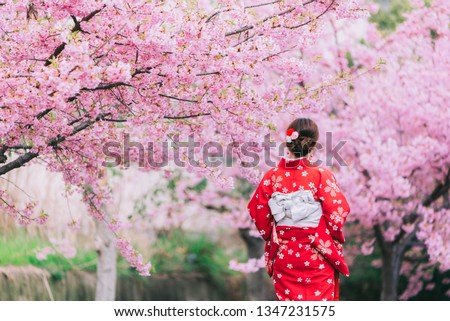 An outdoors woman in a garden with a pink cherry blossom walks full length along a path strewn with  Stock photo © ElenaBatkova