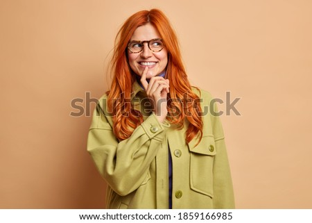 Optimistic foxy woman with glad expression, looks into distance, wears shades, long dress, strolls o Stock photo © vkstudio