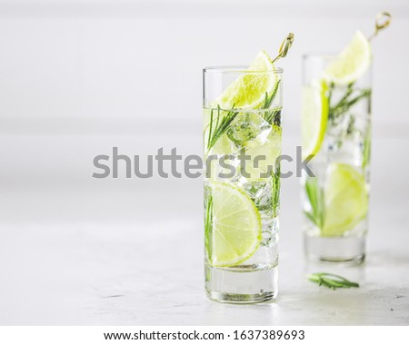 Refreshing lemon lime drink with ice cubes in glass goblets agai Stock photo © artsvitlyna