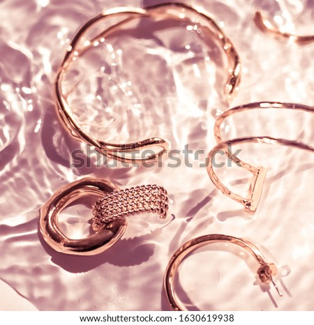 Golden bracelets, earrings, rings, jewelery on pink water backgr Stock photo © Anneleven