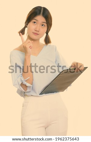 Image of woman pointing finger while holding blank thought bubbl Stock photo © deandrobot