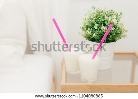 Two glasses of vanilla milkshake on bedside table for breakfast, vase of green plant near, Fresh bev Stock photo © vkstudio