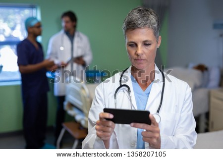 Front view of matured Caucasian female doctor using mobile phone in clinic at hospital. Colleagues a Stock photo © wavebreak_media