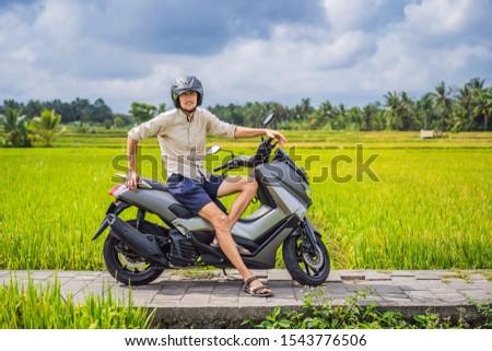 Male traveler on a bike among a rice field. Tourist travels to Bali BANNER, LONG FORMAT Stock photo © galitskaya