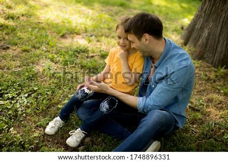 Pai solteiro sessão grama árvore pequeno filha Foto stock © boggy