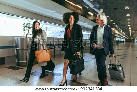Woman traveler walking through airport terminal going to gate carrying purse and carry-on hand lugga Stock photo © Maridav
