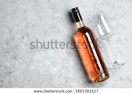 Bottle of pink rose wine with grapes and empty glass with corkscrew and linen cloth on light backgro Stock photo © DenisMArt