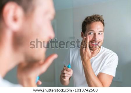 Smiling young man putting face cream under eyes to treat wrinkles or undereye eyebags, Anti-aging fa Stock photo © Maridav
