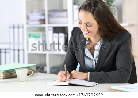 happy woman sitting at office using pen and diary to check her p stock photo © hasloo
