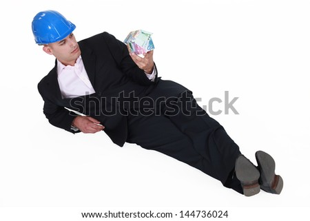 Engineer lazily lying on the floor and staring at a house made of money Stock photo © photography33