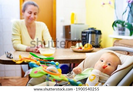 A daughter and her mother seated at a table and laughing together. stock photo © photography33