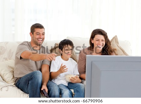 Family laughing while watching television together in the living Stock photo © HASLOO