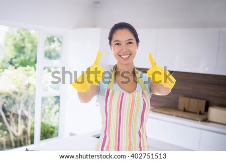 Composite image of happy woman giving thumbs up in rubber gloves Stock photo © wavebreak_media