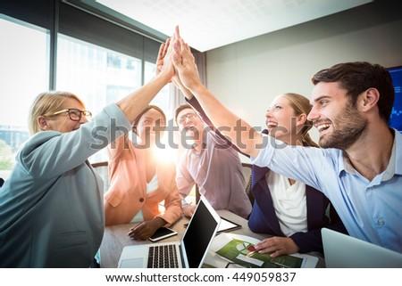 Team of business executives giving high five at desk Stock photo © wavebreak_media