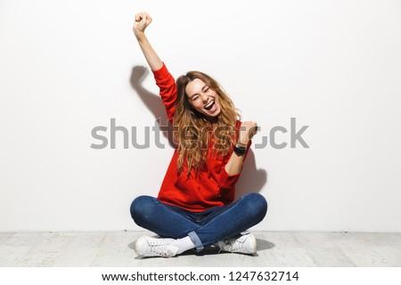 Stock photo: Portrait of joyous woman 20s wearing sweatshirt laughing, isolat