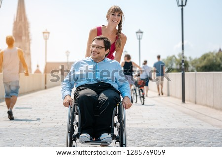 Woman and her friend in a wheelchair having stroll through the town Stock photo © Kzenon