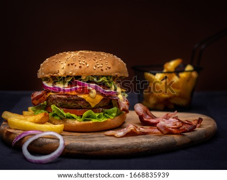 Stock photo: Closeup of fresh burger with French fries on wooden table with bowls of tomato sauce. lifestyle food
